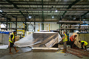 Polythene sheeting being placed over loaded PMC